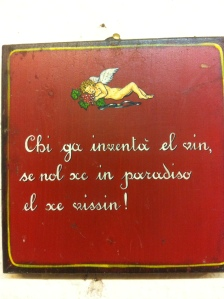 Venetian language sign on a Prosecco farm: Who invented the wine is either in heaven or near ii